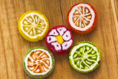 Five round colorful lollipops on wooden table,top view Stock Photo