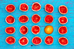 Five rows of ruby red grapefruit halves. With one overturned against a bright blue background stock photo
