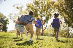 Five school kids running in a field, back view, close up stock photos
