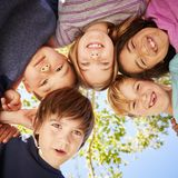 Five schoolchildren standing in a circle and smiling royalty free stock images