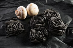 Five servings of black pasta with cuttlefish ink and two mushroo Royalty Free Stock Photography
