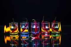 Five shot glasses full of drink and with the red chili peppers l. Ying inside them and one pepper in front of them behind which the flame burns on a black stock photography