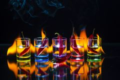 Five shot glasses full of drink and with the red chili peppers l. Ying inside them and one pepper in front of them behind which the flame burns on a black royalty free stock photo