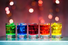 Five shots glasses full of assorted beverages and Royalty Free Stock Photo