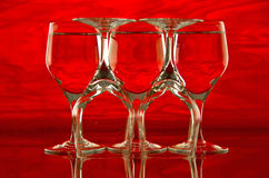 Five Silhouettes. Group of five wine glasses against a background of red patterned glass stock photos