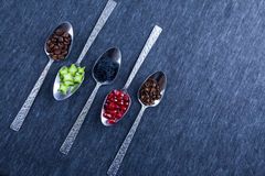 Five silver spoons with food and spices. Stock Images