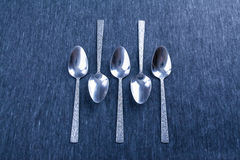 Five silver spoons with pattern. Royalty Free Stock Photos