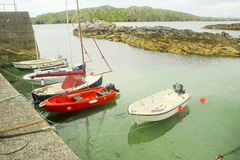 Five Small Boats at a Dock, Lewis, Scotland. Five small  boats moored at a concrete dock at Lewis, Scotland. One is a sailboat and the other four are outboards Royalty Free Stock Photography