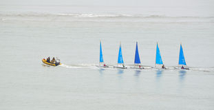 Five small Colourful Sailing Dinghies being towed by a small inflatable power boat. Stock Image