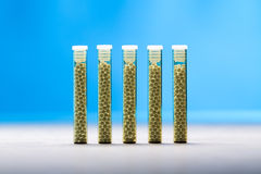 Five small glass tubes with homeopathy globules Royalty Free Stock Photo