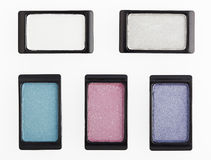 Five small multicolored eyeshadows on white Royalty Free Stock Photo