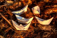 Five small paper origami boats in the rays of the setting sun Stock Image