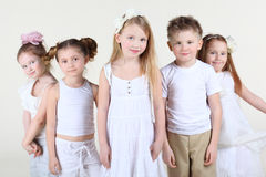 Five smiling children stand and look at camera. Five smiling children in white clothes stand and look at camera. Focus on center girl royalty free stock photos