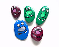 Five smiling faces of monsters. Painted acrylic pebbles. Stock Image