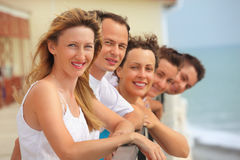Five smiling friends on balcony. Summer stock images
