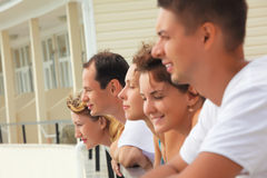 Five smiling friends on balcony. Summer royalty free stock image