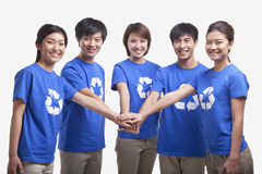 Five smiling and happy young people in a row wearing recycling symbol t-shirts with hands together, studio shot Royalty Free Stock Photo