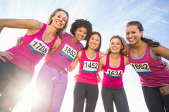 Five smiling runners supporting breast cancer marathon Stock Image