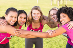 Five smiling runners supporting breast cancer marathon. Portrait of five smiling runners supporting breast cancer marathon in parkland Royalty Free Stock Photos
