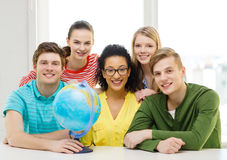 Five smiling student with earth globe at school Stock Photo