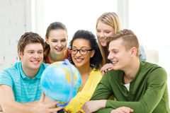 Five smiling student looking at globe at school Royalty Free Stock Image