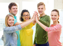 Five smiling students giving high five at school stock images