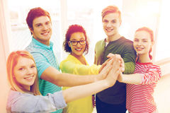 Five smiling students giving high five at school Stock Photography