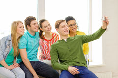 Five smiling students taking picture with camera Royalty Free Stock Image