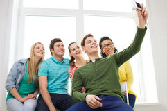 Five smiling students taking picture with camera Stock Photography