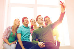 Five smiling students taking picture with camera Royalty Free Stock Photo
