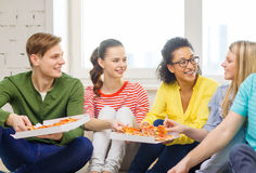 Five smiling teenagers eating pizza at home. Food, leisure and happiness concept - five smiling teenagers eating pizza at home Royalty Free Stock Photo