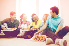 Five smiling teenagers eating pizza at home Stock Image
