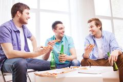 Five smiling teenagers eating pizza at home. Friendship, home, drinks and food concept - happy male friends with beer and pizza at home Stock Photo