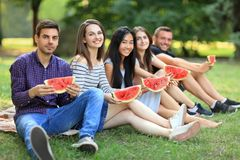 Five smiling women and men with slices of watermelon outdoors Royalty Free Stock Images