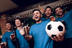 Five soccer fans drinking beer celebrating and cheering at sports bar. They are supporting blue team royalty free stock image