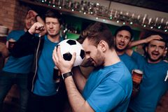 Five soccer fans drinking beer sad that their team looses at sports bar. stock photography
