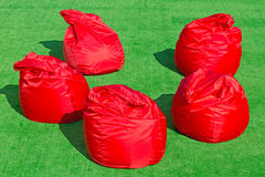 Five soft red chairs in the form of bags on the field Stock Photography