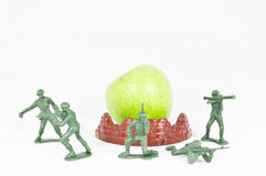 Five Soldier toy protect green apple Royalty Free Stock Image