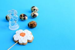 Five speckled quail eggs, a gingerbread in the shape of a flower and a rabbit figurine stock photo