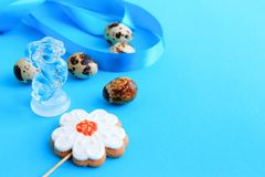 Five speckled quail eggs, a gingerbread in the shape of a flower and a rabbit figurine stock image