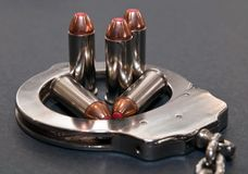 Five 44spl red tipped bullets inside of a metal handcuff stock photo