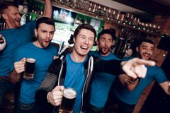 Five sports fans drinking beer celebrating and cheering at sports bar. They are supporting blue team royalty free stock photography