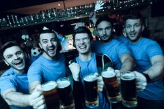 Five sports fans drinking beer celebrating and cheering in front of tv at sports bar. They are supporting blue team stock photos