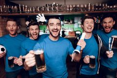 Five sports fans drinking beer celebrating and cheering at sports bar. They are supporting blue team royalty free stock image