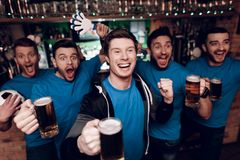 Five sports fans drinking beer celebrating and cheering at sports bar. They are supporting blue team stock images