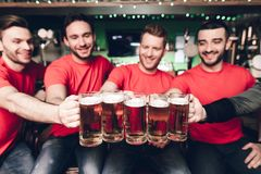 Five sports fans drinking beer cheering at sports bar. They are supporting red team royalty free stock photography