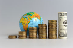 Five stacks of coins with a globe and a bundle of dollars Royalty Free Stock Photos