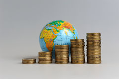Five stacks of coins with a globe Stock Photography