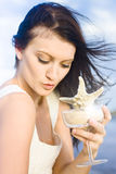 Five Star Holiday. Concept Sees A Happy Woman Drinking From A Star Fish Cocktail With Wind Blowing In Her Brunette Hair Royalty Free Stock Images