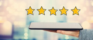 Five Star Rating with tablet computer. Five Star Rating with man holding a tablet computer royalty free stock images